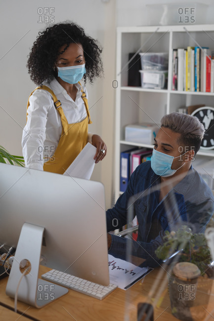 Mixed race male and female creative business colleague talking in office wearing face masks, using a computer. Health and hygiene in workplace during Coronavirus Covid 19 pandemic.