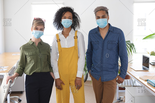 Portrait of a multi ethnic group of three male and female creatives in office wearing face masks, Health and hygiene in the workplace during Coronavirus Covid 19 pandemic.