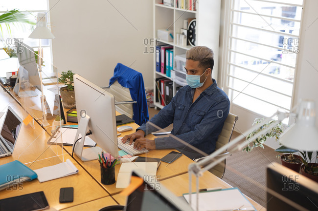 Mixed race male creative sitting at desk in a modern office, wearing a face mask and using a computer. Health and hygiene in the workplace during Coronavirus Covid 19 pandemic.