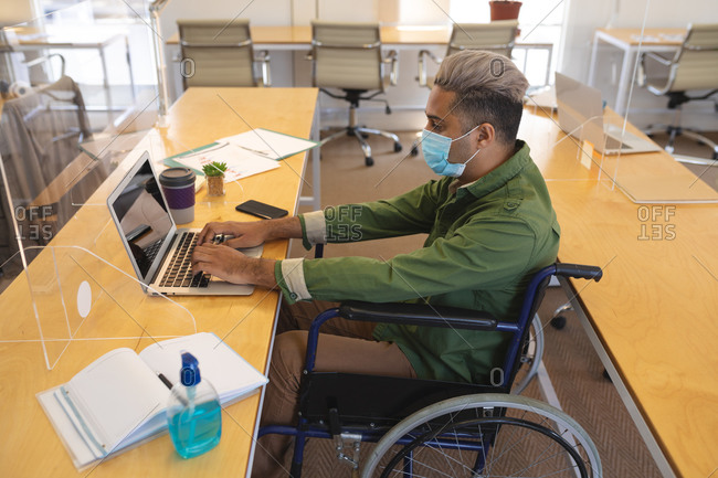 Mixed race male creative sitting in a wheelchair at desk in an office, wearing face mask, using a laptop computer. Health and hygiene in workplace during Coronavirus Covid 19 pandemic.