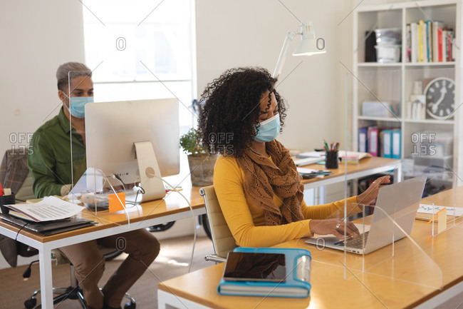Mixed race male and female creatives working at office desks with protective screens, using computers. Health and hygiene in workplace during Coronavirus Covid 19 pandemic.
