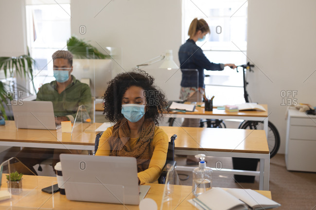 Multi ethnic group of male and female creatives working at office desks with protective screens, using laptop computers. Health and hygiene in workplace during Coronavirus Covid 19 pandemic.