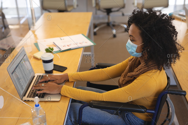 Mixed race female creative sitting in a wheelchair at desk in an office, wearing face mask, using a laptop computer. Health and hygiene in workplace during Coronavirus Covid 19 pandemic.