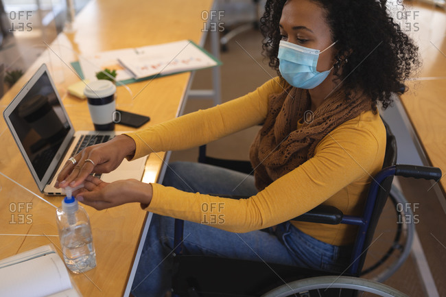 Mixed race female creative sitting in a wheelchair at desk in an office, wearing face mask, disinfecting hands with hand sanitizer. Health and hygiene in workplace during Coronavirus Covid 19 pandemic.