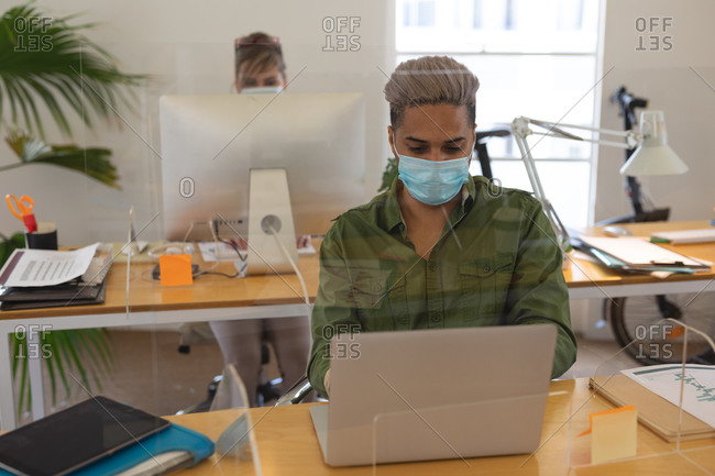 Multi ethnic group of male and female creatives working at office desks with protective screens, using computers. Health and hygiene in workplace during Coronavirus Covid 19 pandemic.