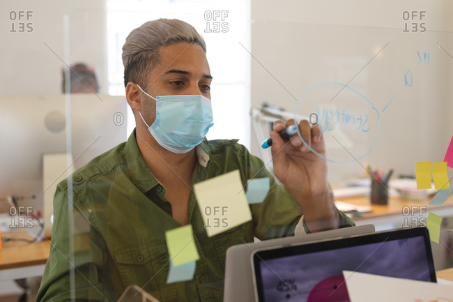 Mixed race male creative in face mask working at desk in office, writing on protective screen. Health and hygiene in workplace during Coronavirus Covid 19 pandemic.