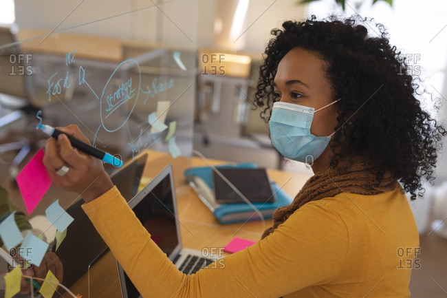 Mixed race female creative in face mask working at desk in office, writing on protective screen. Health and hygiene in workplace during Coronavirus Covid 19 pandemic.