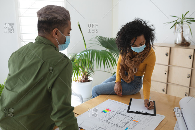 Mixed race male and female architects in office wearing face masks, discussing over architectural drawing. Health and hygiene in workplace during Coronavirus Covid 19 pandemic.