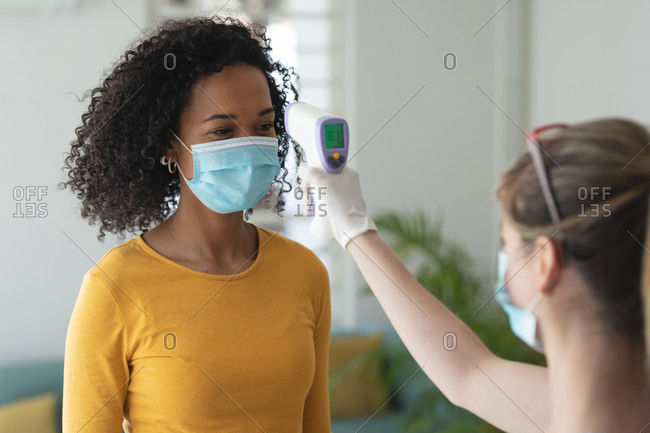Caucasian woman using digital thermometer taking temperature of mixed race woman arriving at work wearing face mask. Health and hygiene in workplace during Coronavirus Covid 19 pandemic.