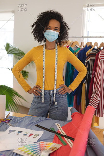 Portrait of mixed race female fashion designer in studio wearing face mask and tape measure around her neck, looking at camera. Health and hygiene in workplace during Coronavirus Covid 19 pandemic.