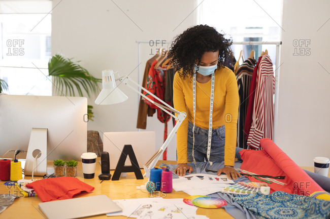 Mixed race female fashion designer working in studio wearing face. Health and hygiene in workplace during Coronavirus Covid 19 pandemic.