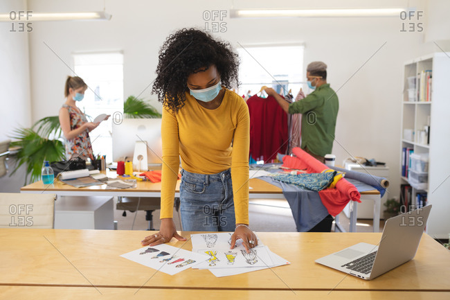 Multi ethnic group of male and female fashion designers working in studio wearing face masks and distancing. Health and hygiene in workplace during Coronavirus Covid 19 pandemic.