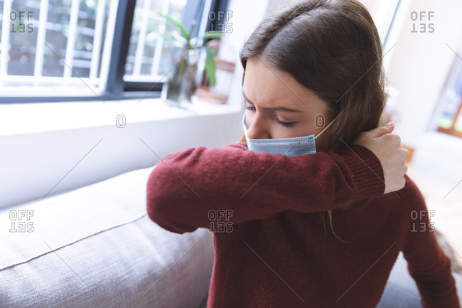 Caucasian woman spending time at home, sitting in living room, wearing face mask, coughing. Social distancing during Covid 19 Coronavirus quarantine lockdown.
