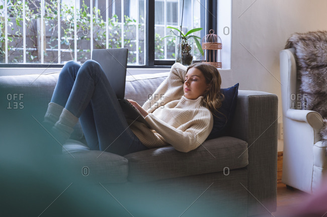 Caucasian woman spending time at home, lying on sofa in sitting room using laptop computer. Social distancing during Covid 19 Coronavirus quarantine lockdown.
