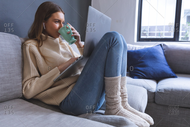 Caucasian woman spending time at home, sitting on sofa in sitting room using laptop computer with earphones, holding mug, drinking. Social distancing during Covid 19 Coronavirus quarantine lockdown.