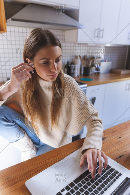 Caucasian woman spending time at home, sitting in kitchen using laptop computer, putting her earphones on. Social distancing during Covid 19 Coronavirus quarantine lockdown.