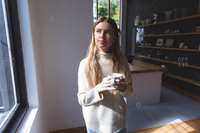 Caucasian woman spending time at home, standing in kitchen, holding green mug looking out of window. Social distancing during Covid 19 Coronavirus quarantine lockdown.