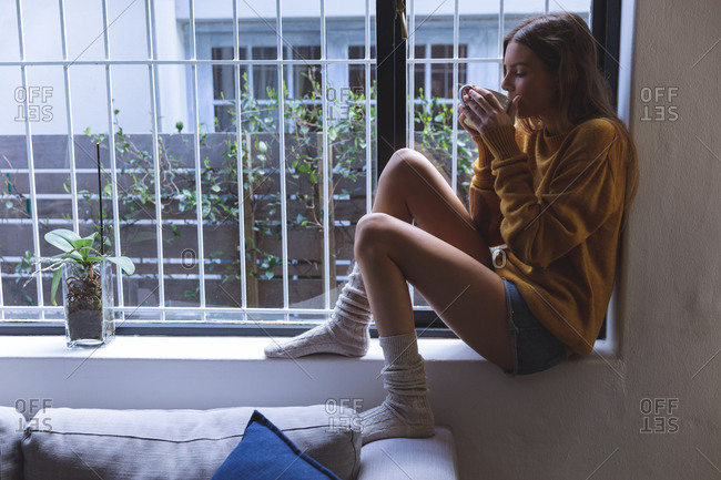 Caucasian woman spending time at home, sitting on windowsill in living room, drinking from green mug. Social distancing during Covid 19 Coronavirus quarantine lockdown.
