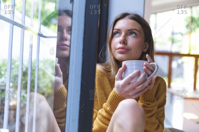 Caucasian woman spending time at home, sitting by window, holding green mug looking out of window. Social distancing during Covid 19 Coronavirus quarantine lockdown.