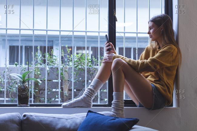 Caucasian woman spending time at home, sitting on windowsill in living room, using smartphone. Social distancing during Covid 19 Coronavirus quarantine lockdown.