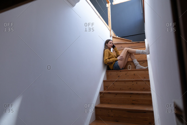 Caucasian woman spending time at home, sitting on stairs in hallway, talking on her smartphone. Social distancing during Covid 19 Coronavirus quarantine lockdown.