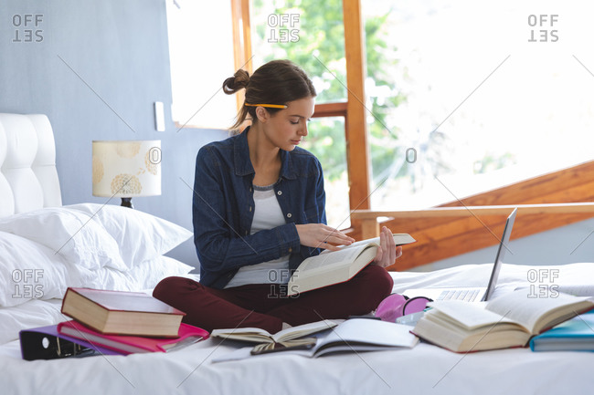 Caucasian woman spending time at home, sitting on bed in bedroom, studying from home, holding and reading book. Social distancing during Covid 19 Coronavirus quarantine lockdown.