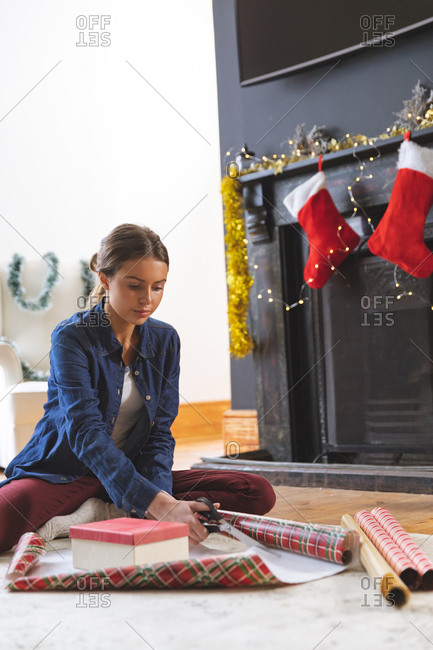 Caucasian woman spending time at home at Christmas, sitting on floor by fireplace in living room, cutting wrapping paper. Social distancing during Covid 19 Coronavirus quarantine lockdown.