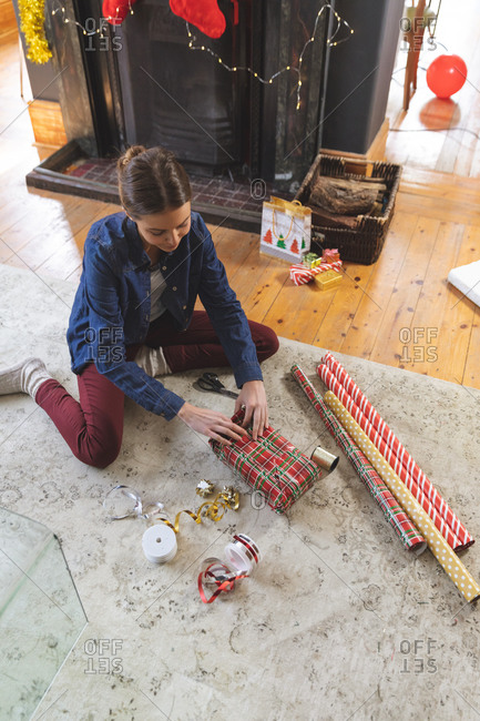 Caucasian woman spending time at home at Christmas, sitting on floor by fireplace in living room, wrapping present in paper. Social distancing during Covid 19 Coronavirus quarantine lockdown.