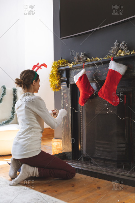 Caucasian woman spending time at home at Christmas, wearing reindeer antlers, sitting on floor in living room, decorating fireplace. Social distancing during Covid 19 Coronavirus quarantine lockdown.