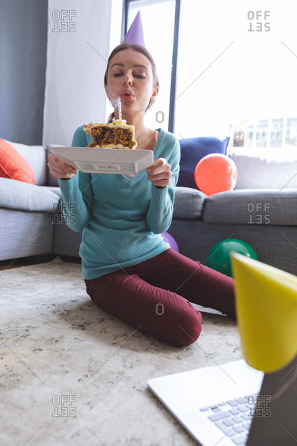 Happy Caucasian woman spending time at home, in party hat, sitting on floor using computer during video chat, blowing off candle. Social distancing during Covid 19 Coronavirus quarantine lockdown.