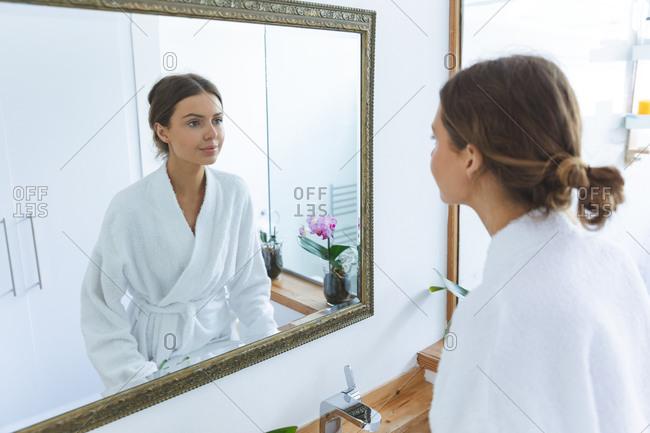 Caucasian woman spending time at home, standing in bathroom, looking in mirror wearing bathrobe. Social distancing during Covid 19 Coronavirus quarantine lockdown.