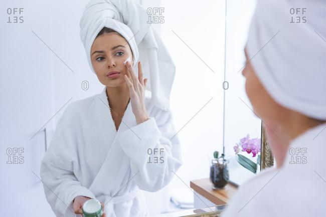 Caucasian woman spending time at home, standing in bathroom, looking in mirror applying face cream. Social distancing during Covid 19 Coronavirus quarantine lockdown.