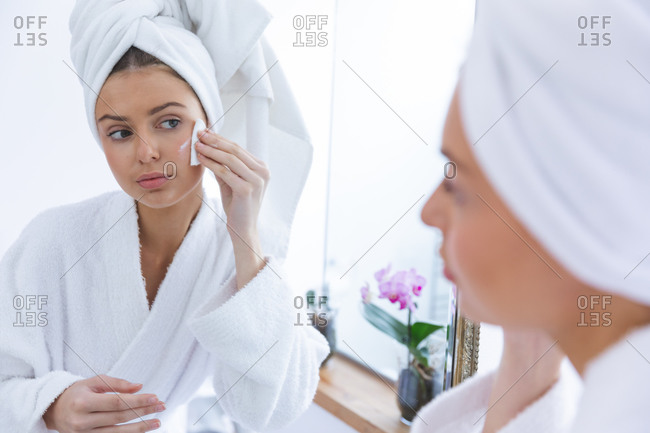 Caucasian woman spending time at home, standing in bathroom, looking in mirror removing make up with cotton pad. Social distancing during Covid 19 Coronavirus quarantine lockdown.