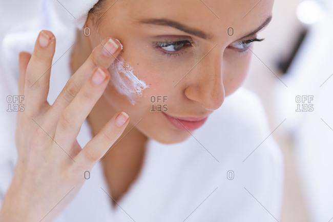 Happy Caucasian woman spending time at home, applying face cream. Social distancing during Covid 19 Coronavirus quarantine lockdown.