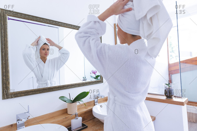 Caucasian woman spending time at home, standing in bathroom, looking in mirror wrapping towel around her hair. Social distancing during Covid 19 Coronavirus quarantine lockdown.