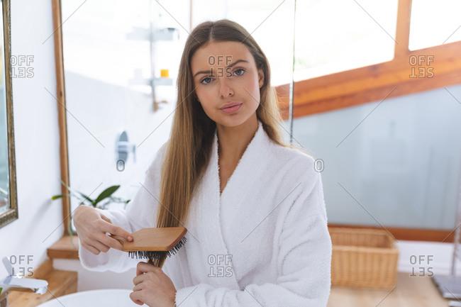 Portrait of Caucasian woman spending time at home, standing in bathroom, looking at camera brushing her hair looking at camera. Social distancing during Covid 19 Coronavirus quarantine lockdown.