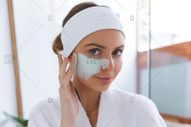 Portrait of Caucasian woman spending time at home, standing in bathroom, looking in mirror applying face mask. Social distancing during Covid 19 Coronavirus quarantine lockdown.