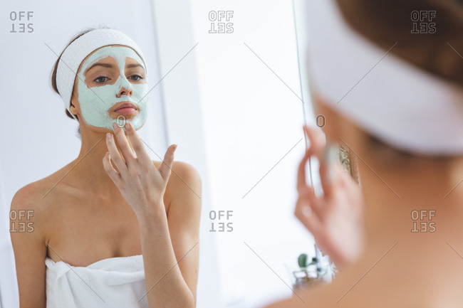 Caucasian woman spending time at home, standing in bathroom, looking in mirror applying face mask. Social distancing during Covid 19 Coronavirus quarantine lockdown.