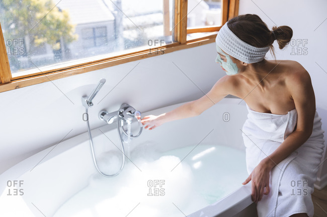 Caucasian woman spending time at home, in bathroom with face mask on, running bath sitting on edge of bathtub. Social distancing during Covid 19 Coronavirus quarantine lockdown.