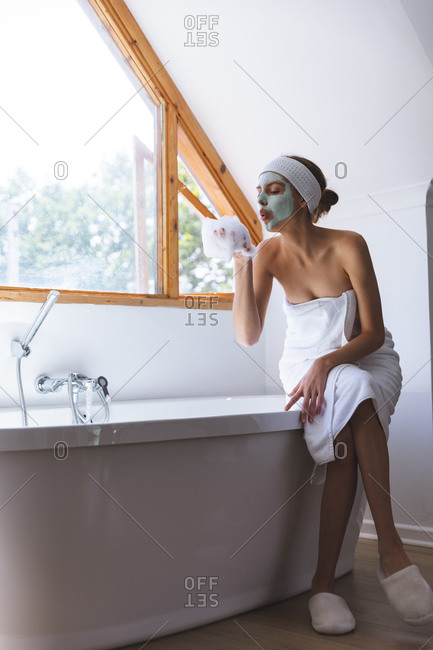 Caucasian woman spending time at home, in bathroom with face mask on, sitting on edge of bathtub blowing foam off her hand. Social distancing during Covid 19 Coronavirus quarantine lockdown.