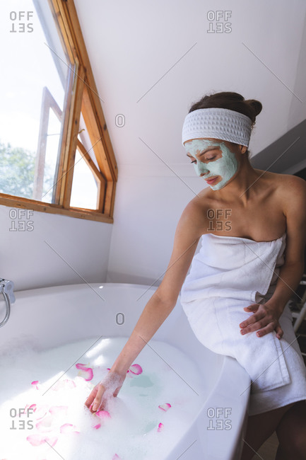 Caucasian woman spending time at home, in bathroom with face mask on, throwing petals in water, sitting on edge of bathtub. Social distancing during Covid 19 Coronavirus quarantine lockdown.