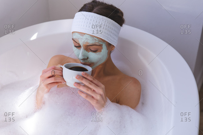 Caucasian woman spending time at home, in bathroom with face mask on, sitting in bathtub, drinking coffee. Social distancing during Covid 19 Coronavirus quarantine lockdown.