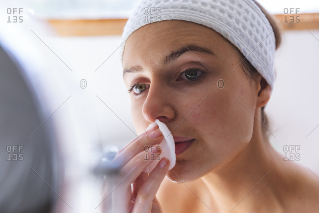 Caucasian woman spending time at home, in bathroom, looking in mirror cleansing her face with cotton pad. Social distancing during Covid 19 Coronavirus quarantine lockdown.