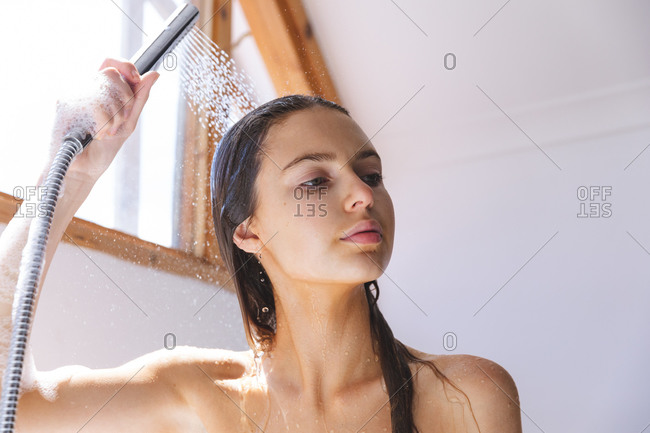 Caucasian woman spending time at home, in bathroom, washing her hair under shower. Social distancing during Covid 19 Coronavirus quarantine lockdown.