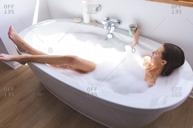 Caucasian woman spending time at home, in bathroom, lying in bathtub, relaxing holding cup. Social distancing during Covid 19 Coronavirus quarantine lockdown.
