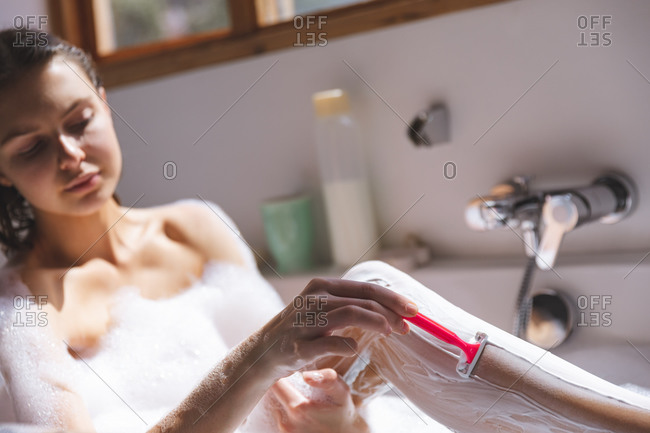 Caucasian woman spending time at home, in bathroom, sitting in bathtub, shaving legs. Social distancing during Covid 19 Coronavirus quarantine lockdown.
