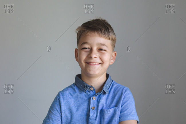 Portrait of happy Caucasian boy spending time at home, smiling and looking at camera on grey background. Social distancing during Covid 19 Coronavirus quarantine lockdown.