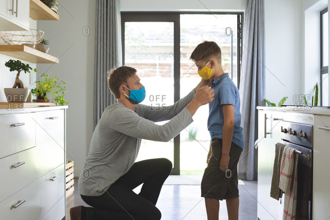 Caucasian man at home with his son, in kitchen, wearing face masks, man helping his son. Social distancing during Covid 19 Coronavirus quarantine lockdown.