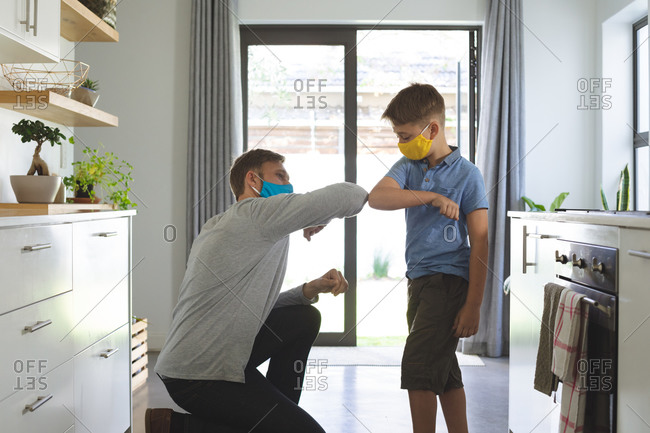 Caucasian man at home with his son, in kitchen, wearing face masks, greeting touching elbows. Social distancing during Covid 19 Coronavirus quarantine lockdown.