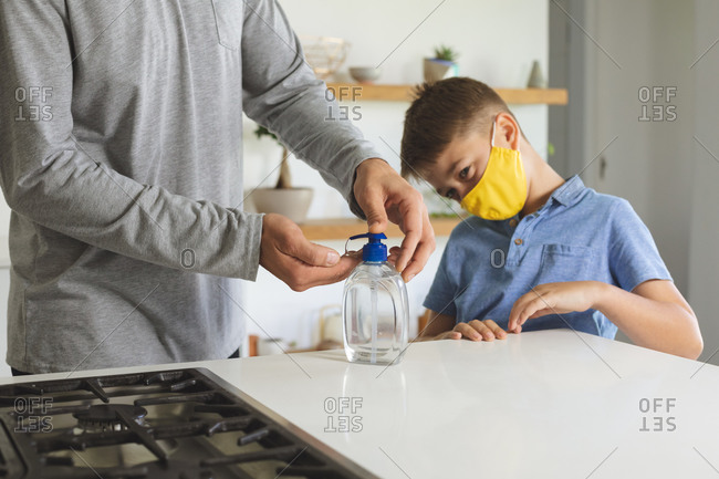 Caucasian man at home with his son, in kitchen, boy wearing face mask, man sanitizing his hands. Social distancing during Covid 19 Coronavirus quarantine lockdown.